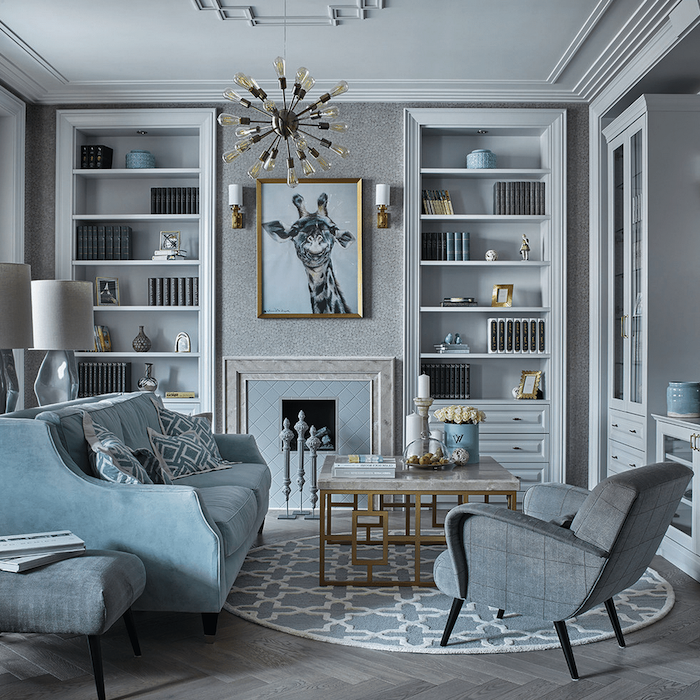 light grey walls, wooden flooring, blue sofa with printed throw pillows, large bookshelves, painting above a fireplace, hanging chandelier, marble coffee table, room ideas
