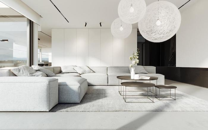 white walls, white floor with white carpet, large white corner sofa, metal coffee tables, white hanging chandeliers, home decor ideas for living room