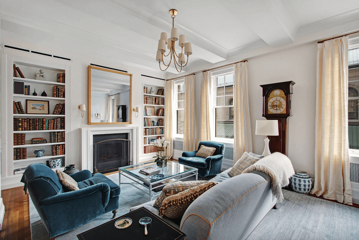 white walls, light grey floor, grey sofa and blue armchairs with printed throw pillows, large bookshelves, mirror above a fireplace, light blue carpet, room ideas