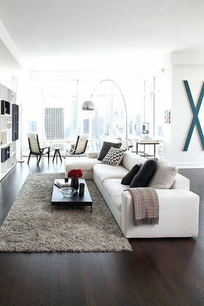 white walls, dark wooden floors, large white sofa with black and grey throw pillows, light grey carpet, small wooden coffee table, living room design ideas