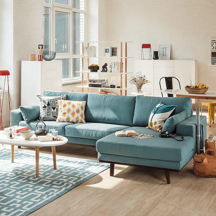 white walls with a wooden floor, blue couch with printed black, blue and yellow throw pillows, blue and white geometrical carpet, small wooden coffee table, living room decorating ideas