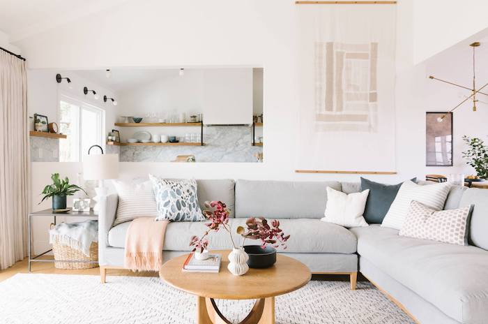 white walls, light grey corner sofa with black, light pink and white printed throw pillows, small wooden coffee table, sitting room ideas