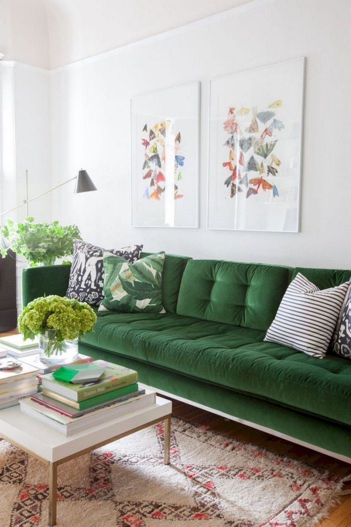 white wall, olive green velvet couch with printed throw pillows, printed carpet, small wooden coffee table, small living room decorating ideas