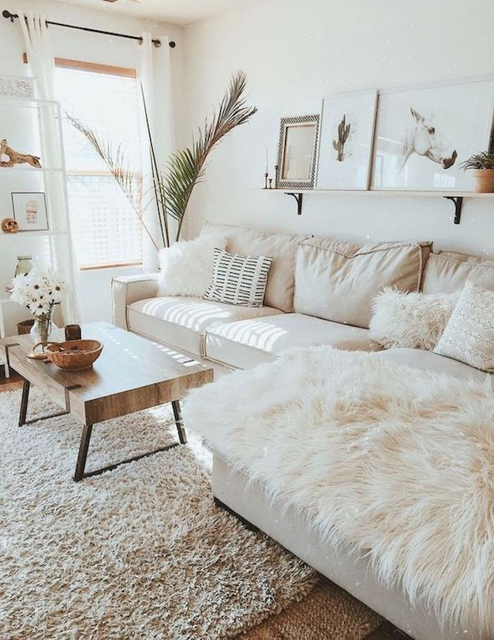 white walls, white corner sofa with white printed throw pillows, cream carpet, small wooden coffee table, small living room decorating ideas