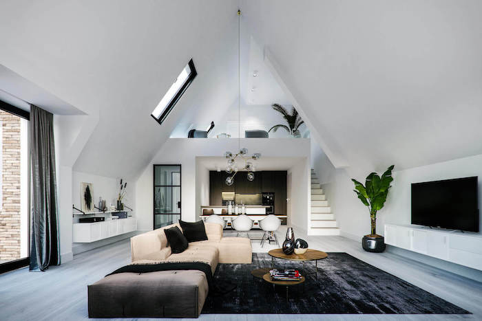 white walls, high ceiling, wooden floor with black carpet, beige sofa with black throw pillows, small wooden coffee table, living room ideas pinterest