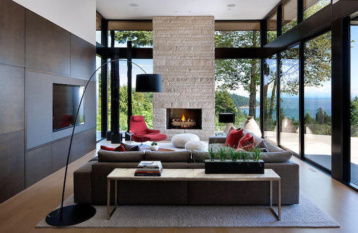 wooden bookshelves, wooden floor with light grey carpet, brick wall with a fireplace, dark grey sofa with red throw pillows, modern contemporary design