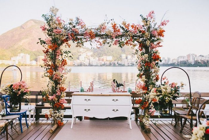 pink and red flowers arch, antique white dresser, aisle leading to the lake, wedding decoration ideas