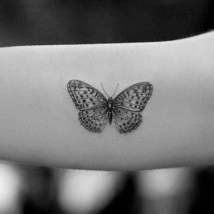 butterfly tattoo on the forearm, tattoo ideas for women, black background