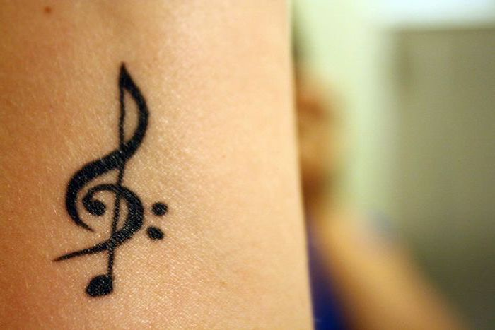 music key tattoo on the arm, blurred background, cute tattoos for girls