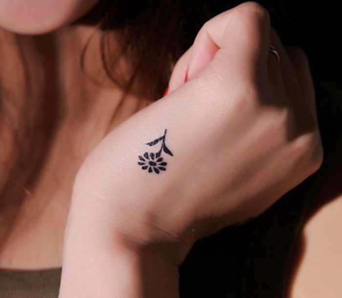 flower tattoo on the hand, long brown hair, tattoos for girls on hand, ring on the finger