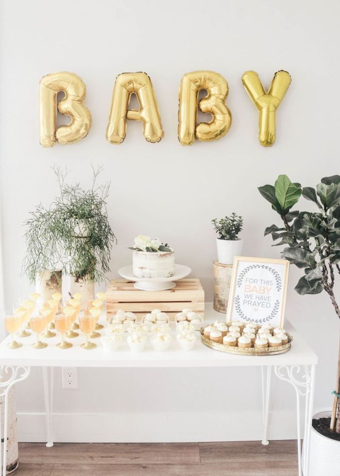 baby gold balloons, cake and sweets on the table, white backdrop, baby shower themes for boys, flowers in pots