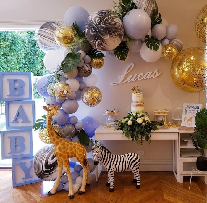 large baby cubes, big balloon arch, giraffe and zebra toys, baby shower decoration ideas for boy, flowers and greenery