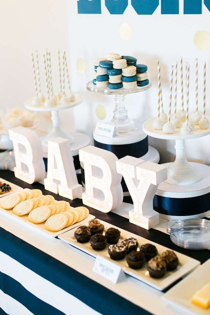 blue and white macaroons, baby shower ideas for boys, baby wooden letters, cookies and sweets on the table