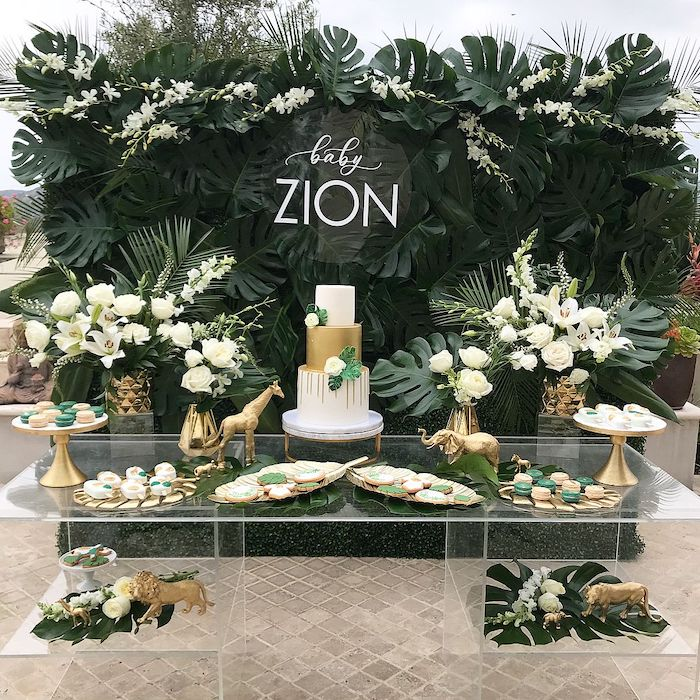 lots of greenery and white flowers, cake and sweets on a glass table, baby shower decoration ideas for boy