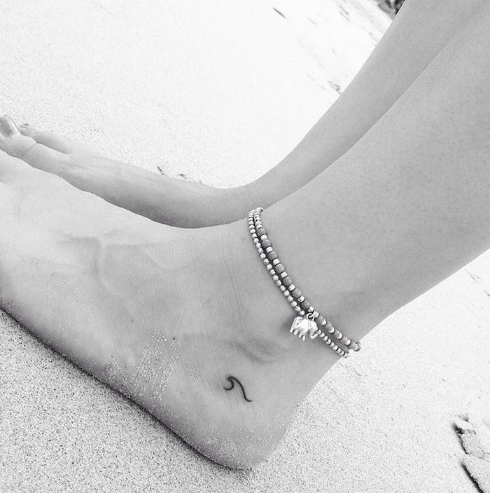 wave tattoo below the ankle, ankle bracelets, tattoos for girls on hand, legs in the sand on the beach