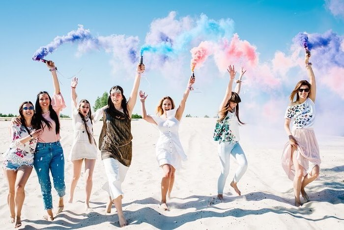 group of women on the beach, colour bombs in the air, feet in the sand, bachelorette party ideas