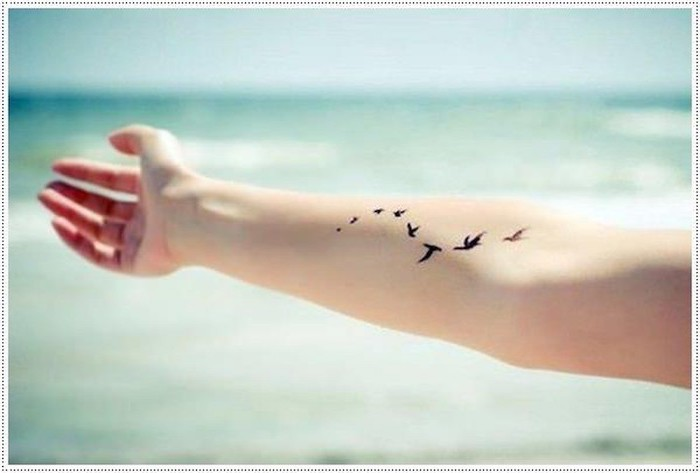 arm in the air, birds tattoo on the forearm, meaningful tattoo ideas, ocean waves in the background