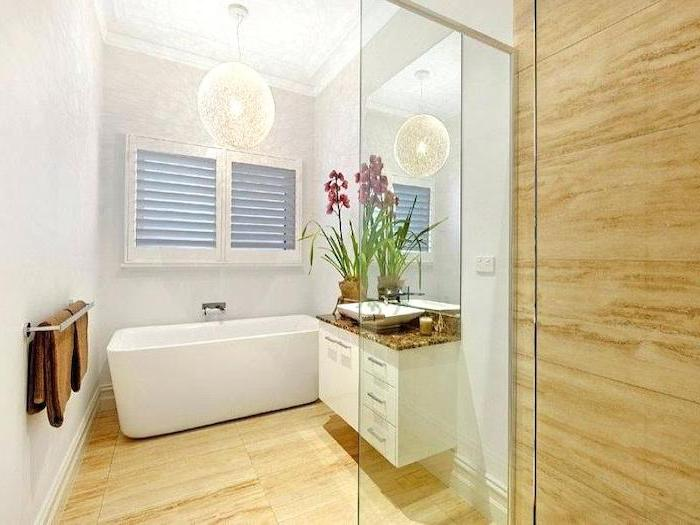 beige tiled walls and floor, white bathtub, white floating cabinets, how to decorate a small bathroom