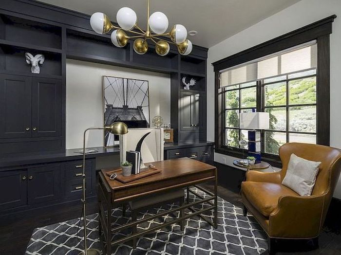 black bookcase with shelves and cupboards, hanging chandelier, wooden desk, work office decorating ideas, white armchair
