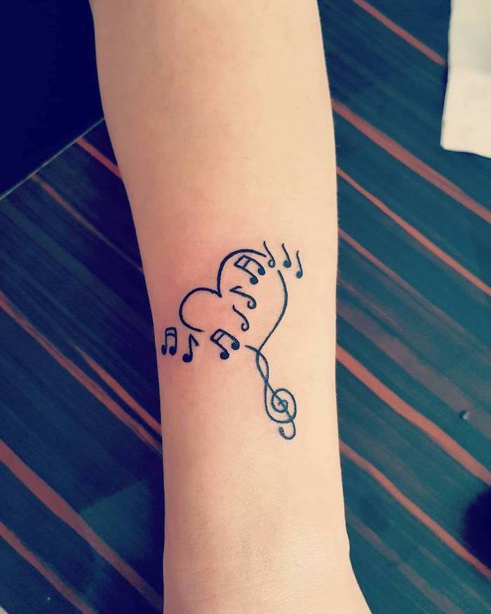 musical notes in the shape of a heart, tattoos for girls, tattoo on the forearm