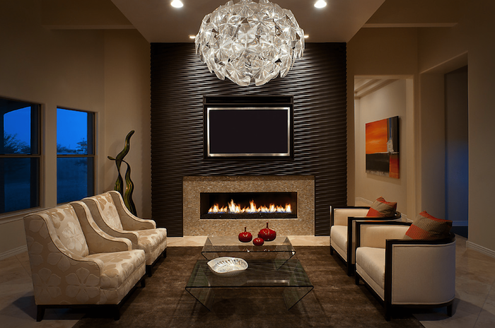 hanging chandelier, accent wall living room, brown wall installation above the fireplace, beige armchairs