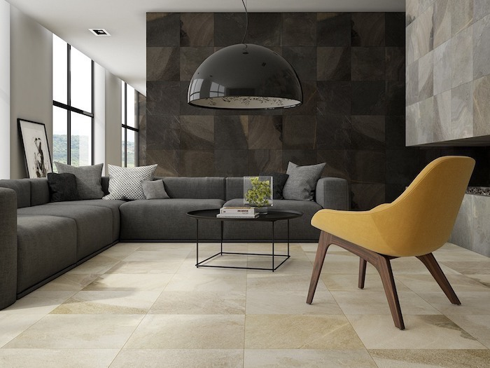 yellow chair, wall treatments, grey corner sofa, white and black stone tiles on the walls