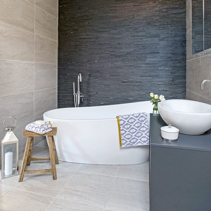 grey stone tiled wall, bathroom shower ideas, white bathtub and sink, grey cabinet, wooden stool