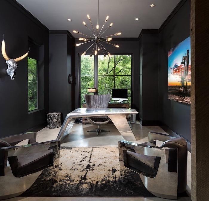 black walls, hanging metal chandelier, metal desk, large velvet grey armchair, small office ideas