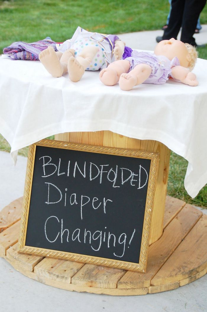 blindfolded diaper changing, chalk board, small baby dolls, unique baby shower themes, wooden table