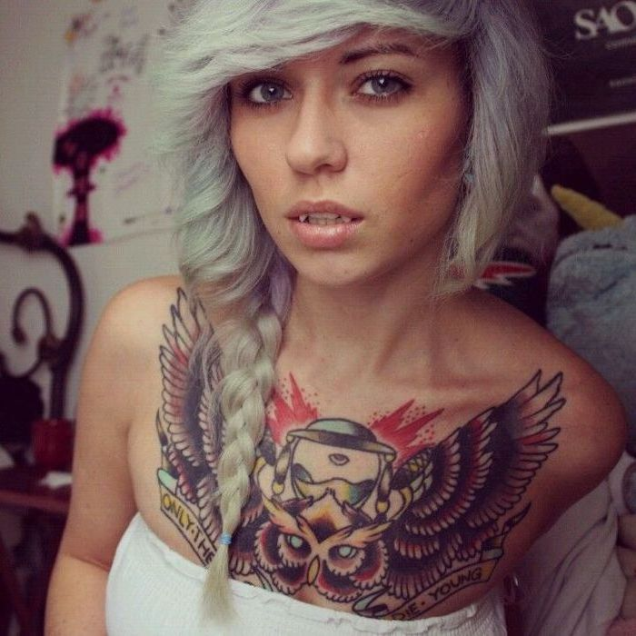blonde and blue braided hair, large wings and owl colourful tattoo, tattoo between breast, white top
