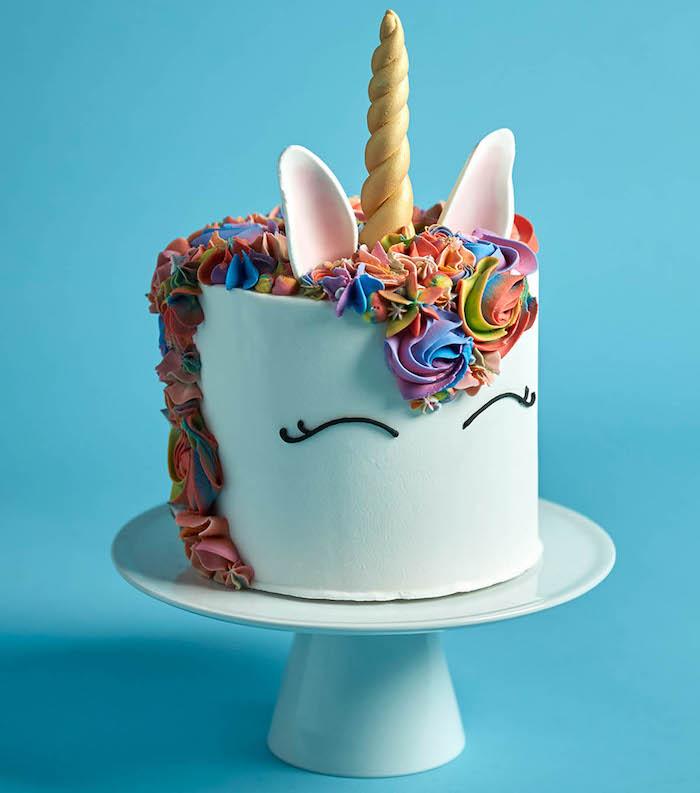 rainbow coloured roses, blue background, unicorn cake ideas, white cake stand