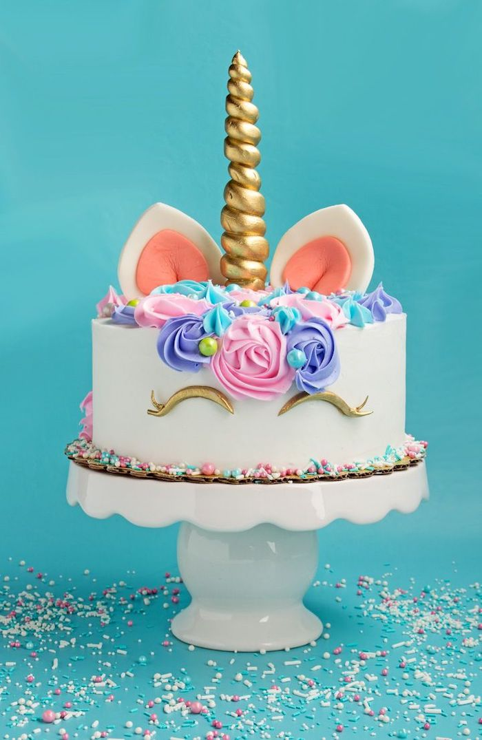 sprinkles on the blue countertop, how to make a unicorn cake, pink purple and blue roses on white fondant