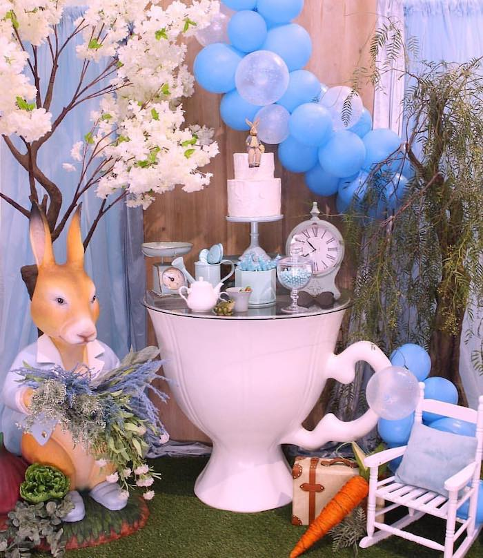 blue balloons, peter rabbit figure, cake and sweets on the table, baby shower decoration ideas for boy