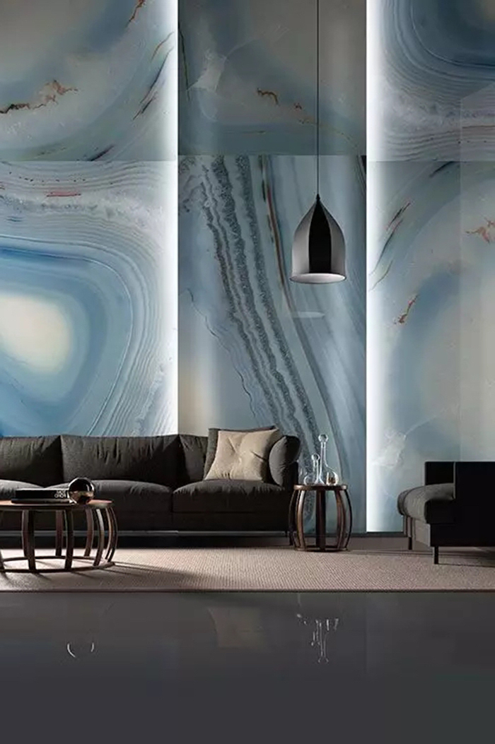 blue marble tiled wall with lights, living room wall colors, black sofa and armchair, hanging lamp