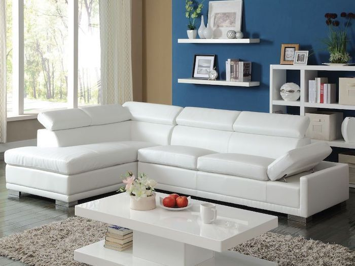 white corner sofa, blue wall with white bookshelves, dining room wall decor, white coffee table
