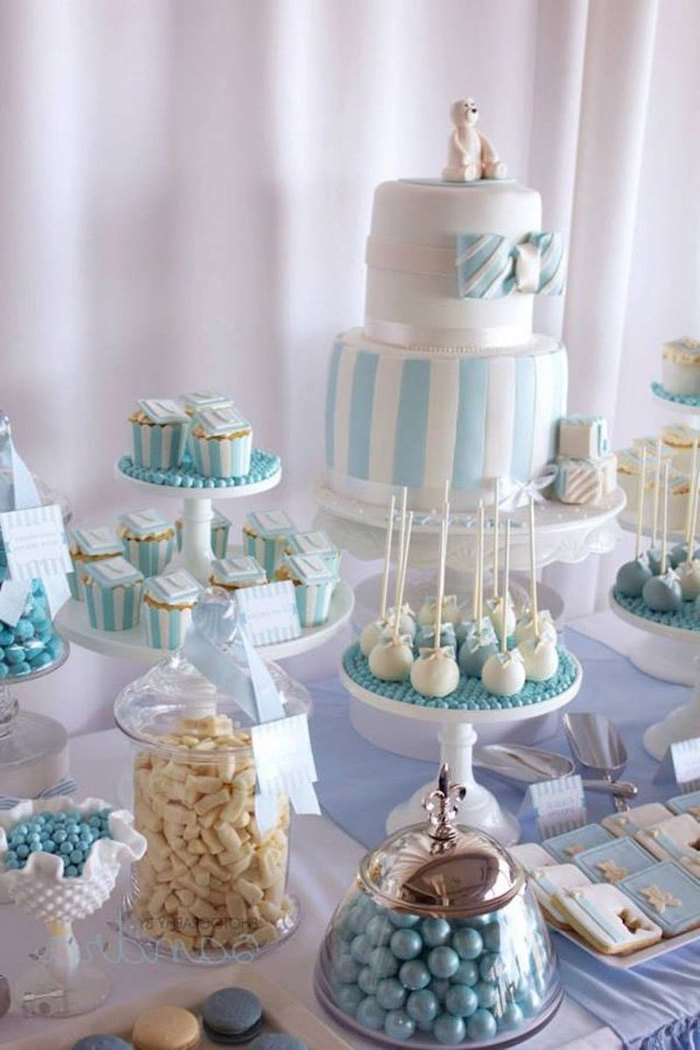 white and blue cake and sweets on the table, baby shower party ideas, jars of candy,