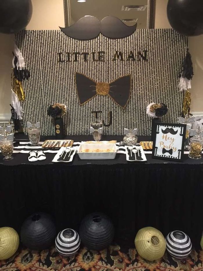 white and black backdrop, moustache and black bow on the wall, baby shower centerpieces boy, black and gold lanterns