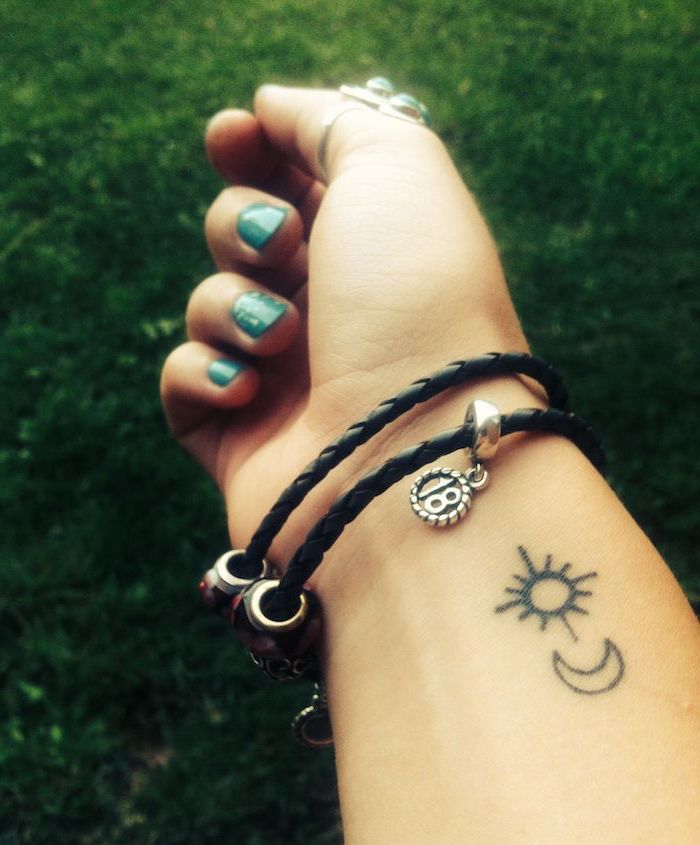 sun and moon tattoo on the wrist, chest tattoos for females, black bracelet with charms, blue nail polish
