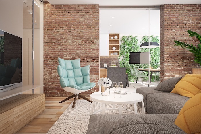 accent wall ideas for living room, brick walls, blue leather armchair, grey and orange sofa