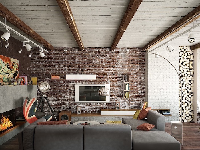 brick wall, grey corner sofa, accent wall, uk flag printed armchair, wooden floor and a fireplace