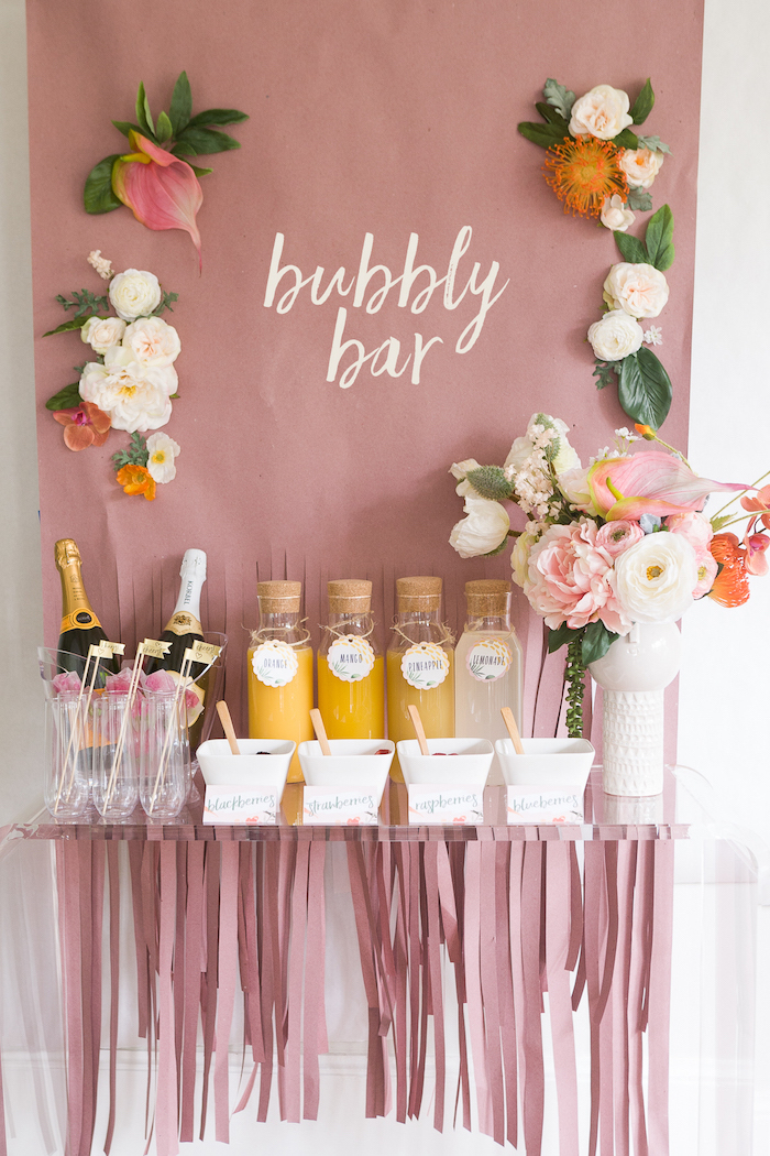 bubbly bar with flowers, champagne bottles, bachelorette party ideas, juices in different bottles