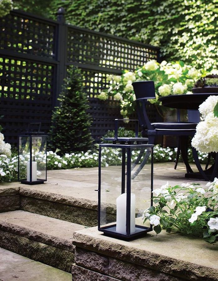 landscaping ideas for front of house, lanterns with candles, flower beds with white flowers, small tree