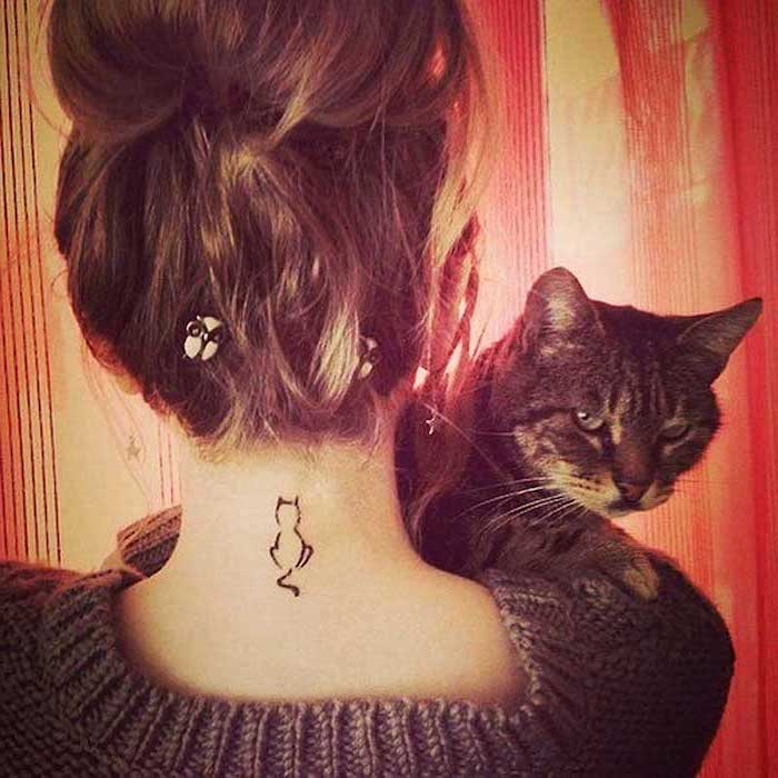 cat tattoo on the neck, angry cat, tattoos for women with meaning, brown hair in a bun, grey blouse
