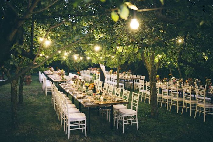 hanging string lights, yellow and orange flower bouquets on the tables, wedding decor