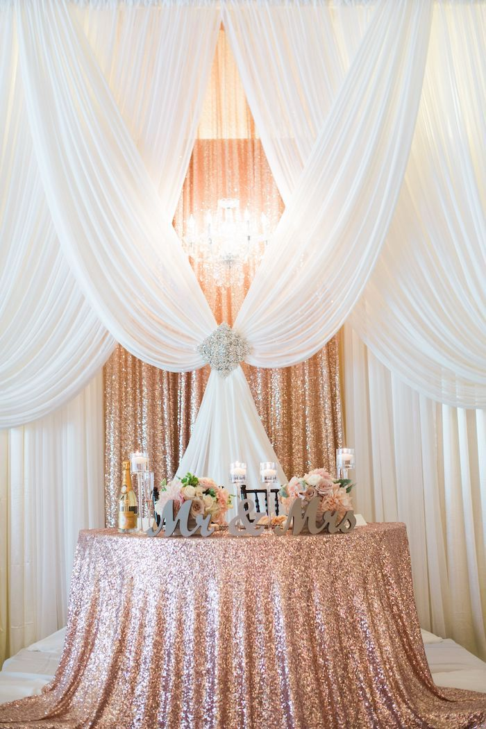 white tulle and rose gold sequin backdrop, mr and mrs wooden sign, candles on the table, diy wedding decorations