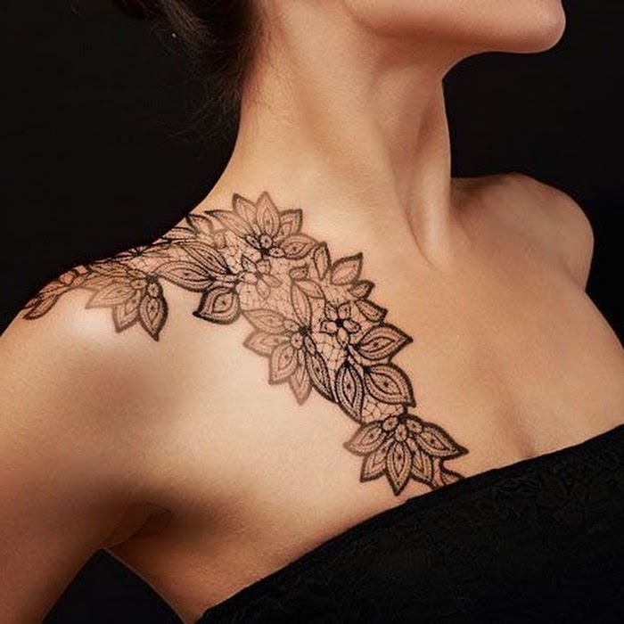 chest tattoos for females, symmetrical flowers on the shoulder, black top and background