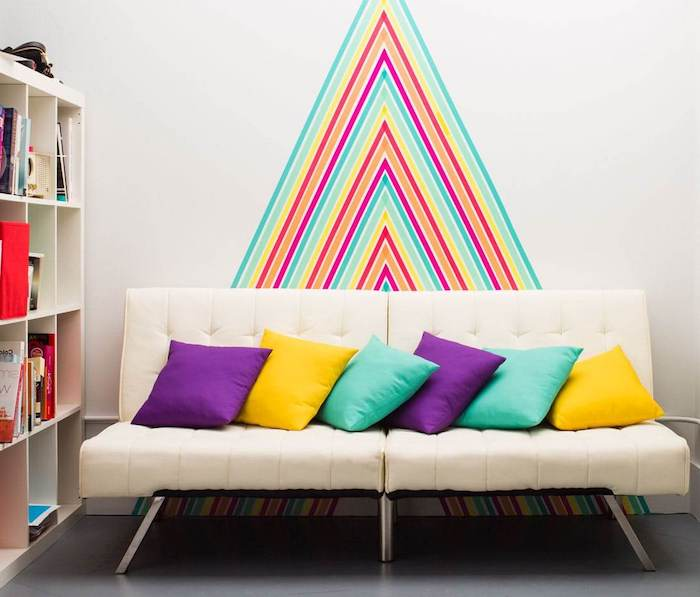 brick accent wall, colourful chevron pattern on the wall, white sofa with throw pillows