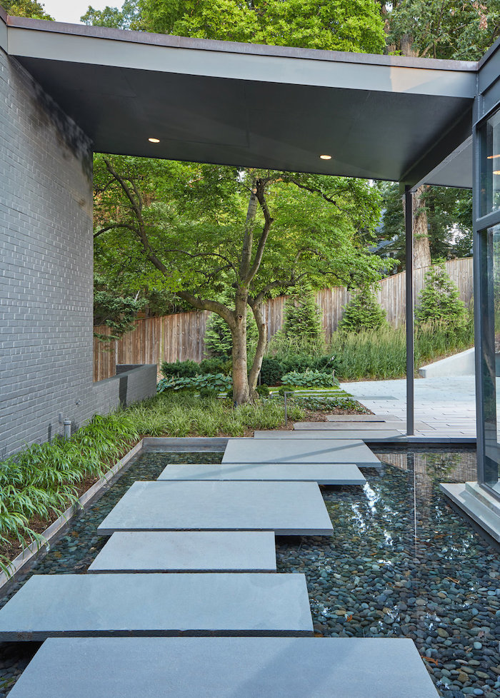 small water pool with rocks in it, geometrical stone tiles pathway, small patches of grass, landscape edging ideas, tall trees