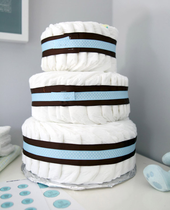 baby shower themes, three tied diaper cake, black and blue ribbon, grey wall background