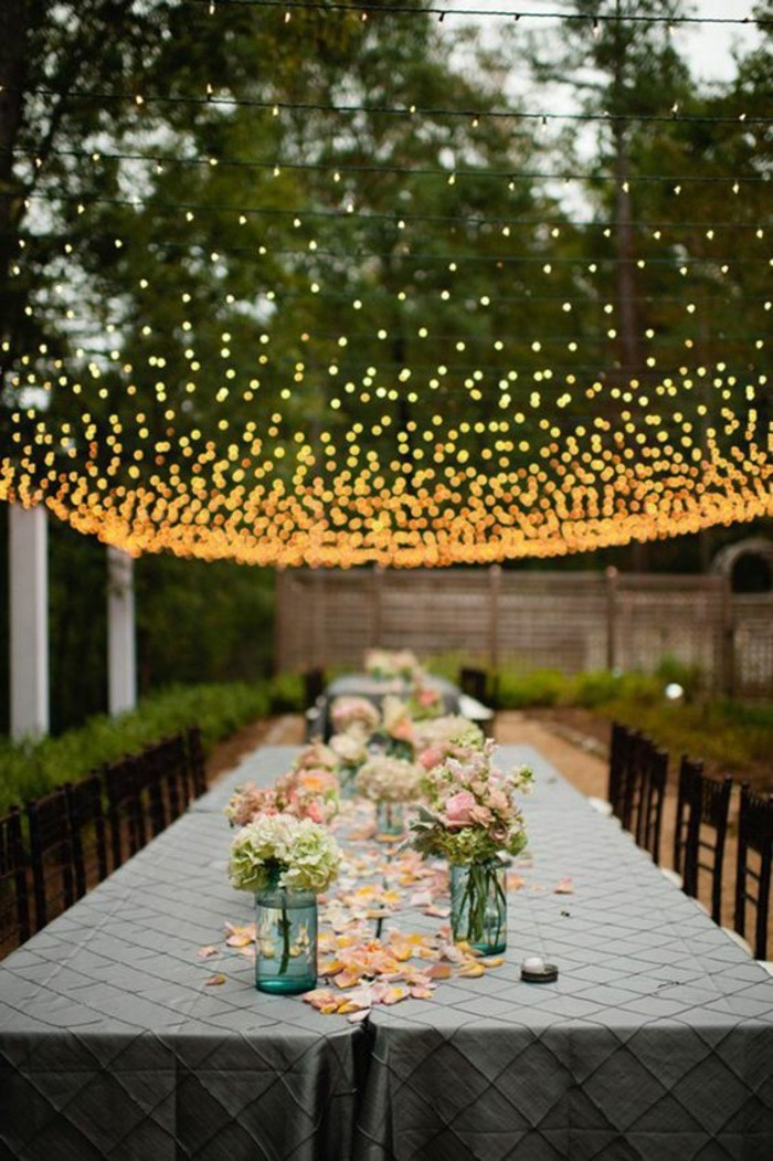 hanging fairy lights, pink and yellow flower bouquets in vases, rose petals on the table, wedding reception decorations